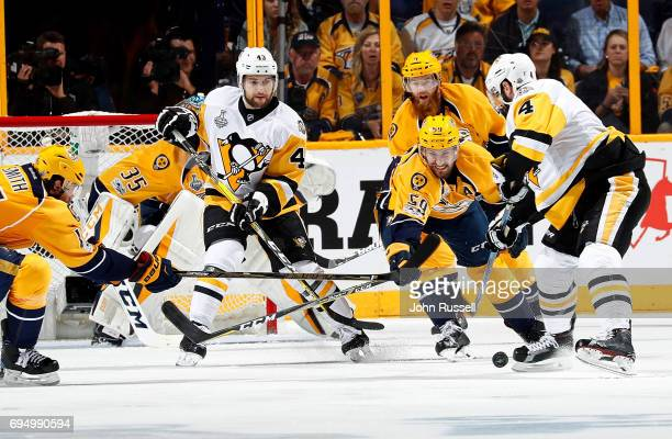 Justin Schultz of the Pittsburgh Penguins tries to settle the puck for a shot as Roman Josi of the Nashville Predators looks to defend while Conor...