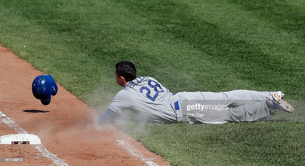 Justin Sellers #28 of the Los Angeles Dodgers slides after being tagged out trying to reach base on a bunt against the Baltimore Orioles at Oriole Park at Camden Yards on April 21, 2013 in Baltimore, Maryland.