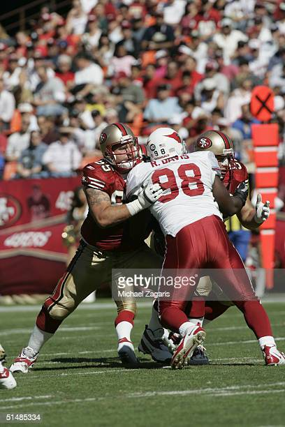 Justin Smiley and Brock Gutierrez of the San Francisco 49ers doubleteam the Arizona Cardinals at Monster Park on October 10 2004 in San Francisco...