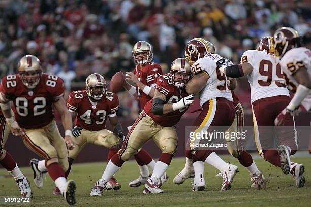 Justin Smiley of the San Francisco 49ers blocks for Ken Dorsey against the Washington Redskins at Monster Park on December 18 2004 in San Francisco...
