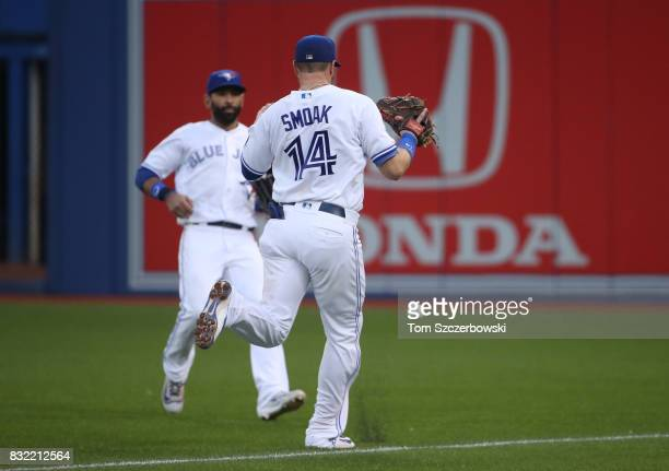 Justin Smoak and Jose Bautista of the Toronto Blue Jays converge but the ball drops in fair territory for a double off the bat of Adeiny Hechavarria...