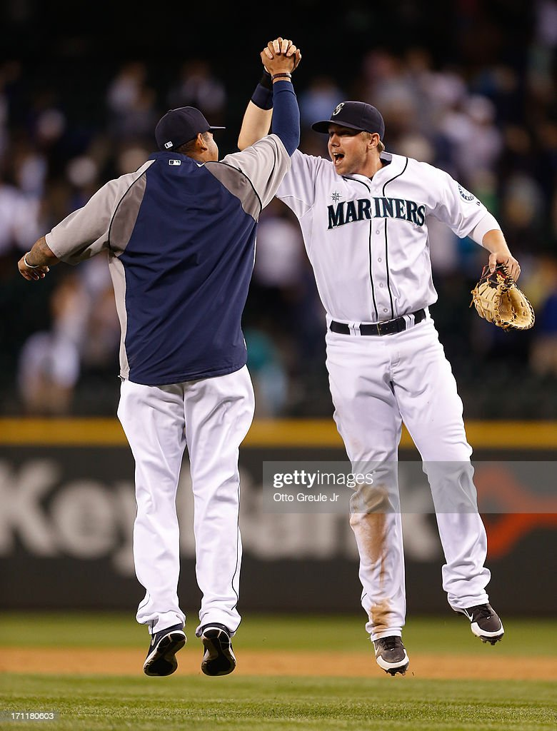 Justin Smoak #17 (R) of the Seattle Mariners celebrates with Felix Hernandez #34 after defeating the Oakland Athletics 7-5 at Safeco Field on June 22, 2013 in Seattle, Washington.