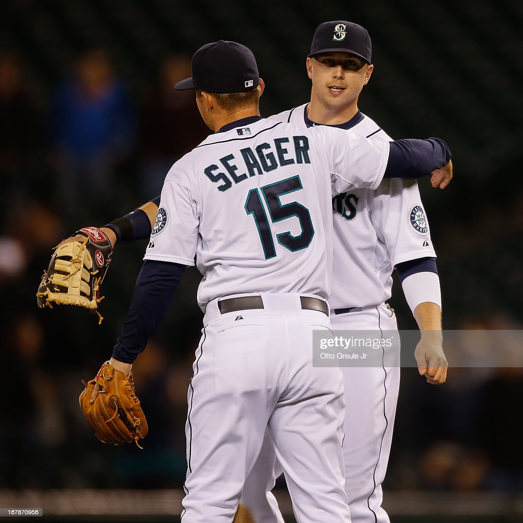 Justin Smoak #17 of the Seattle Mariners celebrates with Kyle Seager #15 after defeating the Baltimore Orioles 8-3 at Safeco Field on May 1, 2013 in Seattle, Washington.