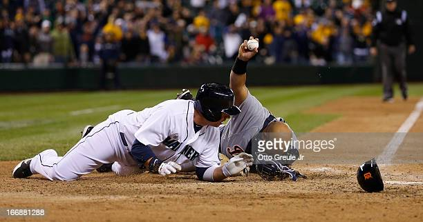 Justin Smoak of the Seattle Mariners is tagged out at home for the final out as catcher Brayan Pena of the Detroit Tigers displays the ball to the...