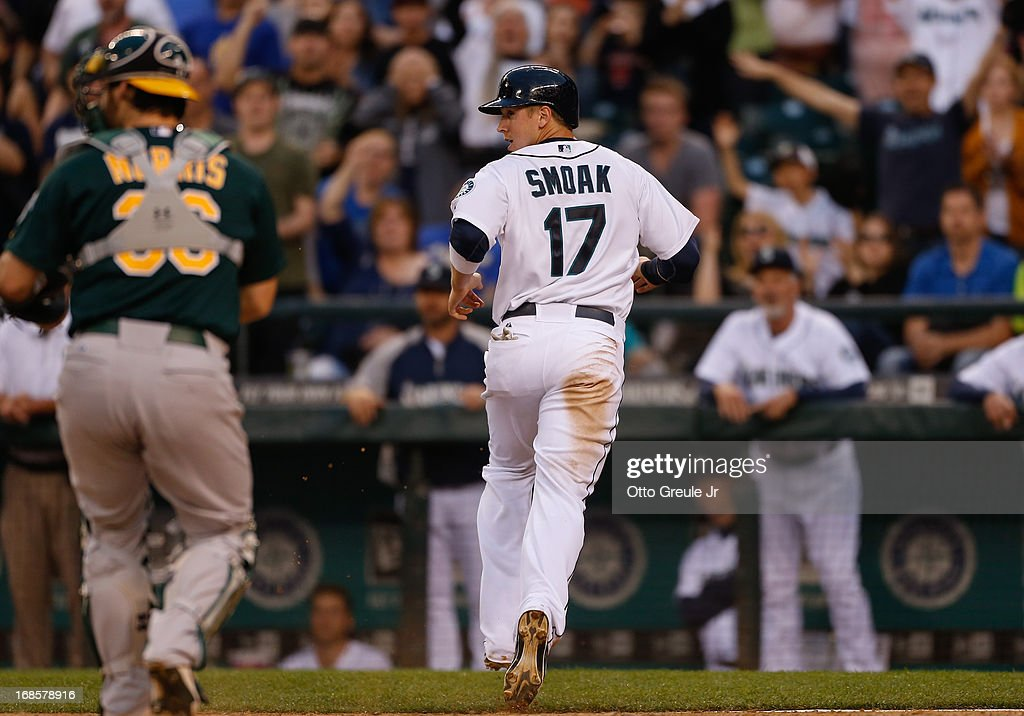 <a gi-track='captionPersonalityLinkClicked' href=/galleries/search?phrase=Justin+Smoak&family=editorial&specificpeople=2350583 ng-click='$event.stopPropagation()'>Justin Smoak</a> #17 of the Seattle Mariners scores on a single by Dustin Ackley in the seventh inning against the Oakland Athletics at Safeco Field on May 11, 2013 in Seattle, Washington.