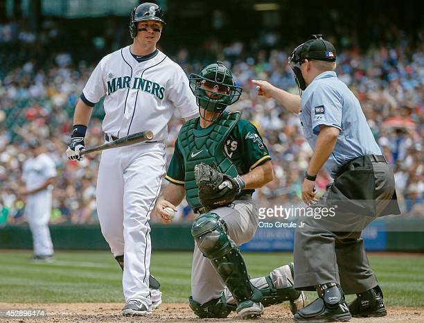 Justin Smoak of the Seattle Mariners steps out of the batters box on a called strike by home plate umpire Mike Muchlinski as catcher John Jaso of the...
