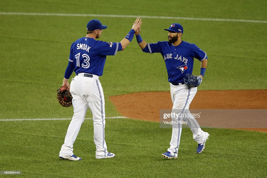 Justin Smoak #13 of the Toronto Blue Jays celebrates with Jose Bautista #19 of the Toronto Blue Jays after defeating the Kansas City Royals 11-8 in game three of the American League Championship Series at Rogers Centre on October 19, 2015 in Toronto, Canada.