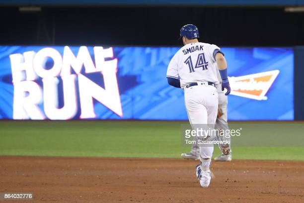 Justin Smoak of the Toronto Blue Jays circles the bases after hitting a tworun home run in the ninth inning during MLB game action against the Boston...