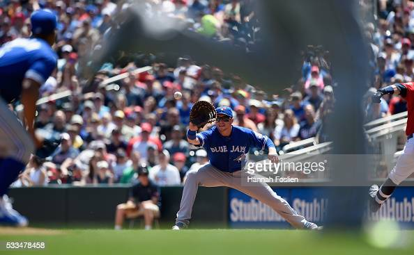 Justin Smoak of the Toronto Blue Jays fields a throw from Josh Donaldson at third base to get Brian Dozier of the Minnesota Twins out at first base...
