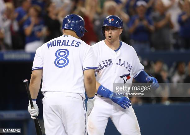 Justin Smoak of the Toronto Blue Jays is congratulated by Kendrys Morales after hitting a gametying tworun home run in the ninth inning during MLB...