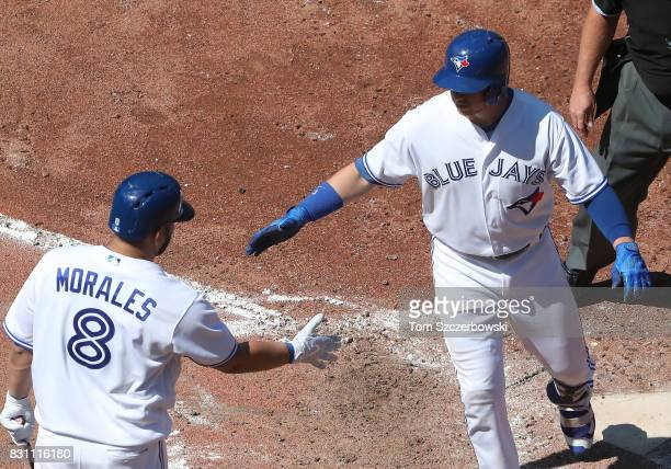 Justin Smoak of the Toronto Blue Jays is congratulated by Kendrys Morales after hitting a solo home run in the seventh inning during MLB game action...