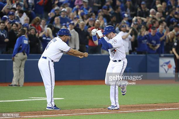 Justin Smoak of the Toronto Blue Jays is congratulated by third base coach Luis Rivera after hitting a gamewinning solo home run in the tenth inning...