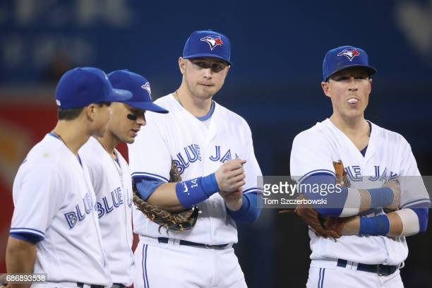 Justin Smoak of the Toronto Blue Jays looks on beside Chris Coghlan and Darwin Barney and Ryan Goins as they congregate on the infield during a...