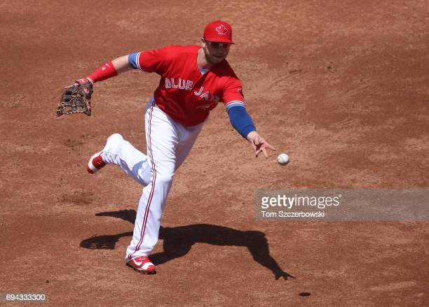 Justin Smoak of the Toronto Blue Jays makes the play and flips the ball to Joe Biagini covering first base to throw out the baserunner in the third...
