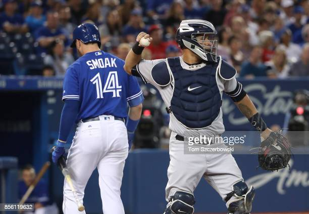 Justin Smoak of the Toronto Blue Jays reacts after striking out swinging in the first inning during MLB game action as Gary Sanchez of the New York...