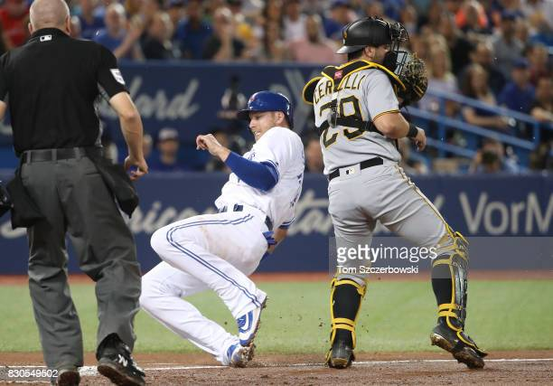 Justin Smoak of the Toronto Blue Jays slides across home plate to score a run on a sacrifice fly in the second inning during MLB game action as...