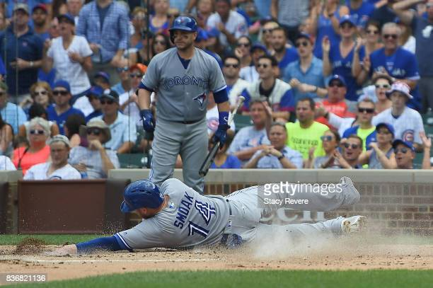 Justin Smoak of the Toronto Blue Jays slides safely into home plate during a game against the Chicago Cubs at Wrigley Field on August 20 2017 in...