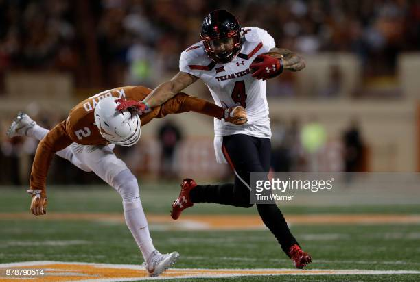 Justin Stockton of the Texas Tech Red Raiders gives a stiff arm to Kris Boyd of the Texas Longhorns in the third quarter at Darrell K RoyalTexas...