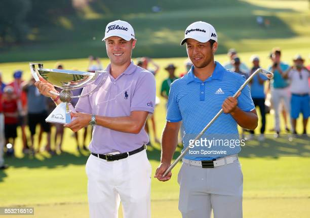 Justin Thomas holds up the FedEx Cup and Xander Schauffele holds up the TOUR Championship trophy after the final round of the TOUR Championship on...