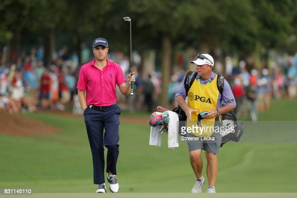 Justin Thomas of the United States and caddie Jimmy Johnson walk up the 18th green during the final round of the 2017 PGA Championship at Quail...