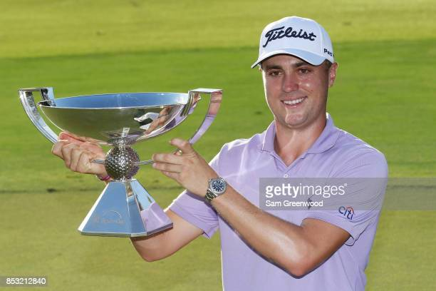 Justin Thomas of the United States celebrates with the trophy on the 18th green after winning the FedExCup and second in the TOUR Championship during...