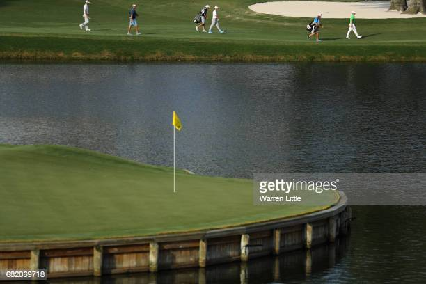 Justin Thomas of the United States Rory McIlroy of Northern Ireland and Dustin Johnson of the United States walk on the 16th hole as the 17th green...