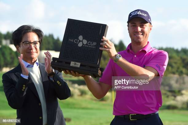 Justin Thomas of the US poses with the trophy as Lee JayHyun chairman of the South Korean food and entertainment giant CJ Group claps during the...