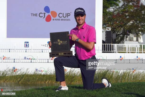 Justin Thomas of the US poses with the trophy at the awards ceremony after winning the CJ Cup golf tournament at Nine Bridges in Jeju Island on...