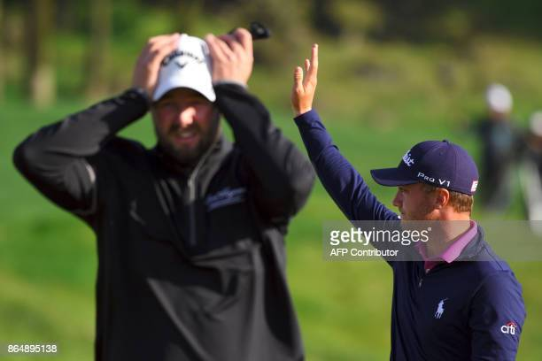 Justin Thomas of the US waves to celebrate his victory as Marc Leishman of Australia walks on the 18th green at the end of the CJ Cup golf tournament...