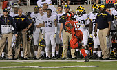 Justin Thomas of the Utah Utes runs past the Michigan Wolverines bench as he scores a 4th quarter touchdown off an interception at RiceEccles Stadium...