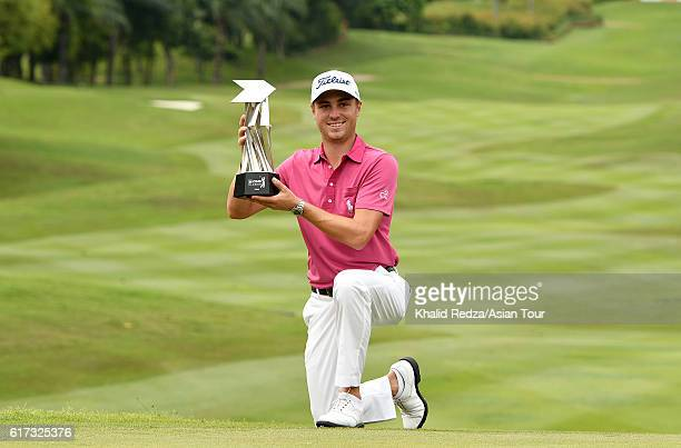 Justin Thomas of United States poses with his trophy after winning on day four of the 2016 CIMB Classic at Kuala Lumpur Golf Country Club on October...