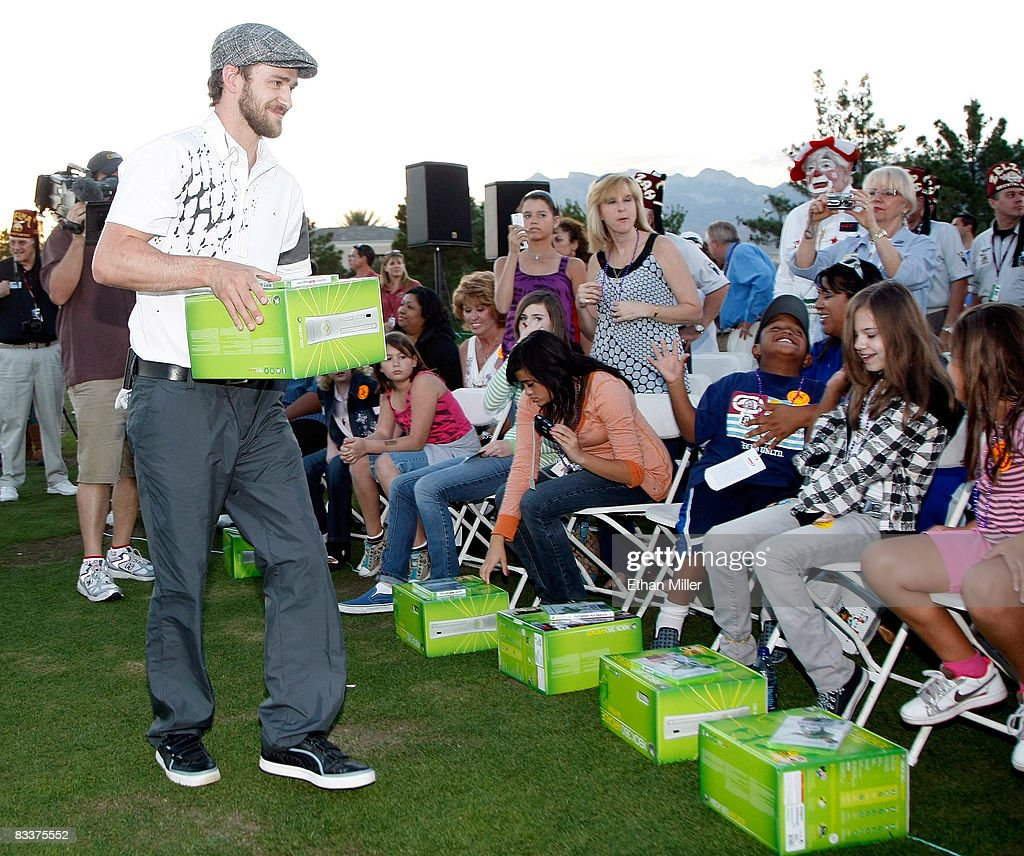 Justin Timberlake hands out Xbox 360 video game consoles to youth from Shriners Hospitals during a golf clinic for kids during the Justin Timberlake...