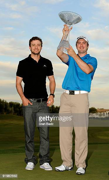 Justin Timberlake left and Martin Laird right pose with the winner's trophy on the 18th green following a three man playoff during the final round of...