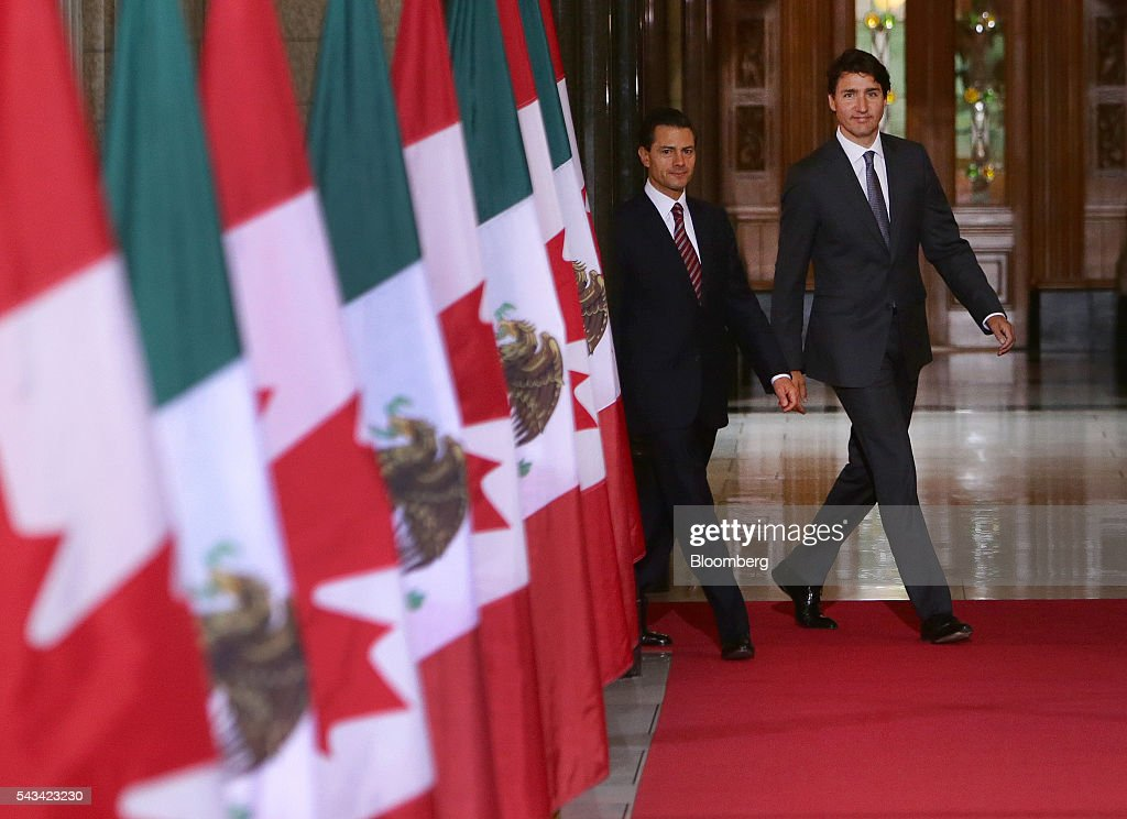 Justin Trudeau, Canada's prime minister, right, and Enrique Pena Nieto, Mexico's president, walk down the Hall of Honour at Parliament Hill ahead of the North American Leaders Summit (NALS) in Ottawa, Ontario, Canada, on Tuesday, June 28, 2016. Trudeau, Nieto, and U.S. President Barack Obama hold the so-called Three Amigos summit Wednesday in Ottawa, with fallout from the U.K.'s vote last week to leave the European Union raising pressure to show confidence in their own alliance. The countries will vow to produce more clean power and cut methane emissions while strengthening economic ties. Photographer: Cole Burston/Bloomberg via Getty Images