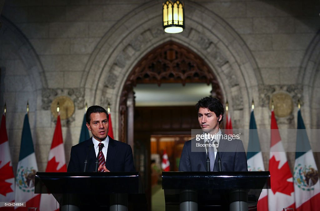 Justin Trudeau, Canada's prime minister, right, listens as Enrique Pena Nieto, Mexico's president, speaks during a joint press conference at Parliament Hill ahead of the North American Leaders Summit (NALS) in Ottawa, Ontario, Canada, on Tuesday, June 28, 2016. Trudeau, Nieto, and U.S. President Barack Obama hold the so-called Three Amigos summit Wednesday in Ottawa, with fallout from the U.K.'s vote last week to leave the European Union raising pressure to show confidence in their own alliance. The countries will vow to produce more clean power and cut methane emissions while strengthening economic ties. Photographer: Cole Burston/Bloomberg via Getty Images
