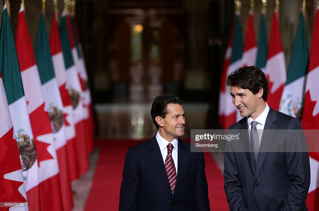 Justin Trudeau, Canada's prime minister, right, smiles with Enrique Pena Nieto, Mexico's president, in the Hall of Honour at Parliament Hill ahead of the North American Leaders Summit (NALS) in Ottawa, Ontario, Canada, on Tuesday, June 28, 2016. Trudeau, Nieto, and U.S. President Barack Obama hold the so-called Three Amigos summit Wednesday in Ottawa, with fallout from the U.K.'s vote last week to leave the European Union raising pressure to show confidence in their own alliance. The countries will vow to produce more clean power and cut methane emissions while strengthening economic ties. Photographer: Cole Burston/Bloomberg via Getty Images