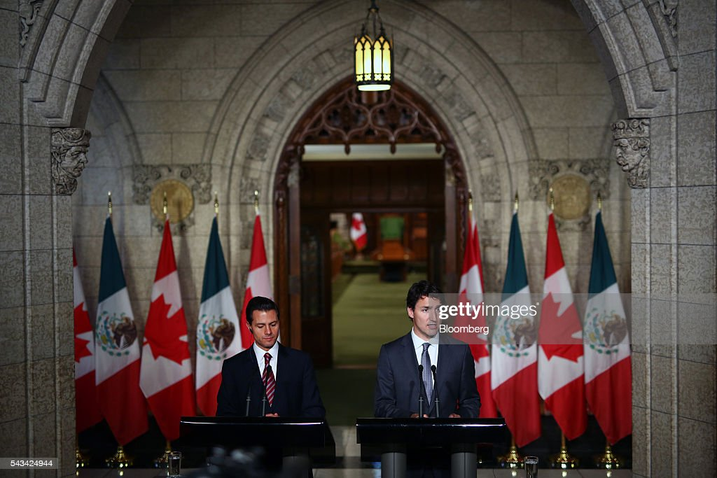 Justin Trudeau, Canada's prime minister, right, speaks as Enrique Pena Nieto, Mexico's president, listens during a joint press conference at Parliament Hill ahead of the North American Leaders Summit (NALS) in Ottawa, Ontario, Canada, on Tuesday, June 28, 2016. Trudeau, Nieto, and U.S. President Barack Obama hold the so-called Three Amigos summit Wednesday in Ottawa, with fallout from the U.K.'s vote last week to leave the European Union raising pressure to show confidence in their own alliance. The countries will vow to produce more clean power and cut methane emissions while strengthening economic ties. Photographer: Cole Burston/Bloomberg via Getty Images
