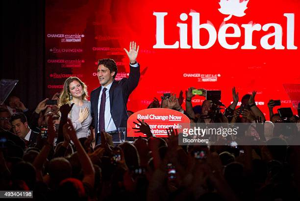 Justin Trudeau Canada's prime ministerelect and leader of the Liberal Party of Canada and his wife Sophie GregoireTrudeau wave to supporters on...