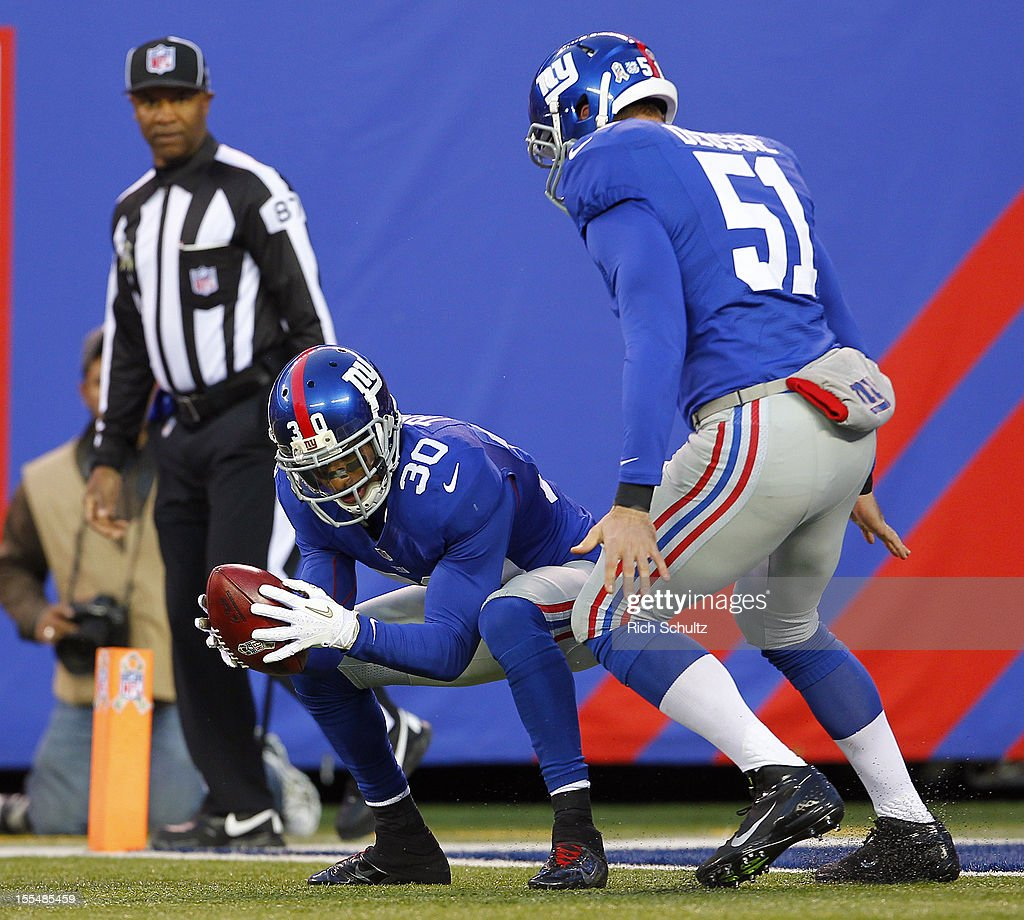 Justin Tryon #30 of the New York Giants downs the ball on the two-yard line as teammate Zak DeOssie #51 looks on after a punt by Steve Weatherford #5 (not pictured) against the Pittsburgh Steelers in the first half during an NFL game at MetLife Stadium on November 4, 2012 in East Rutherford, New Jersey. The Steelers defeated the Giants 24-20.