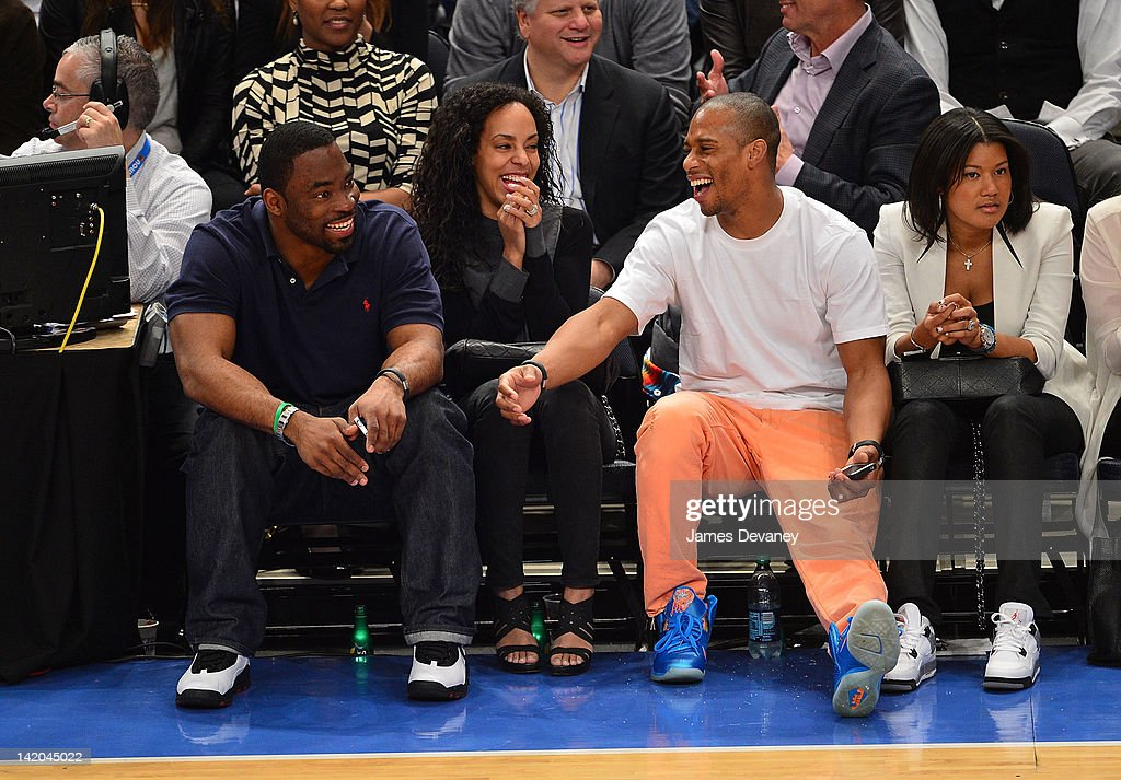 Justin Tuck (L) and Victor Cruz (2nd from R) attend the Orlando Magic vs New York Knicks game at Madison Square Garden on March 28, 2012 in New York City.
