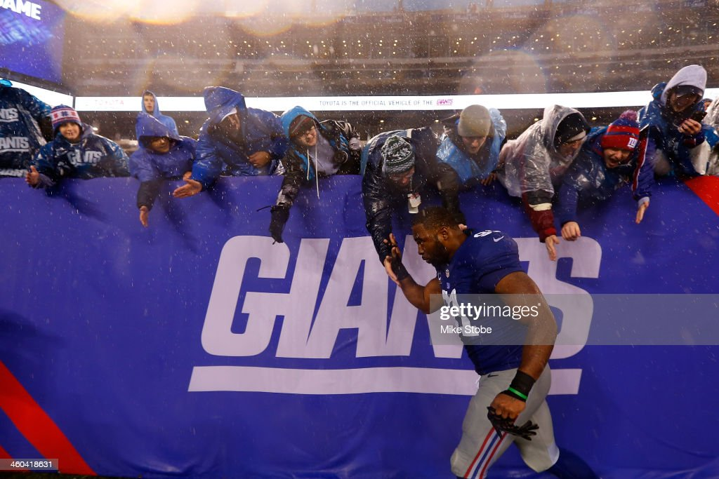 Justin Tuck of the New York Giants highfives the crowd after defeating the Washington Redskins at MetLife Stadium on December 29 2013 in East...