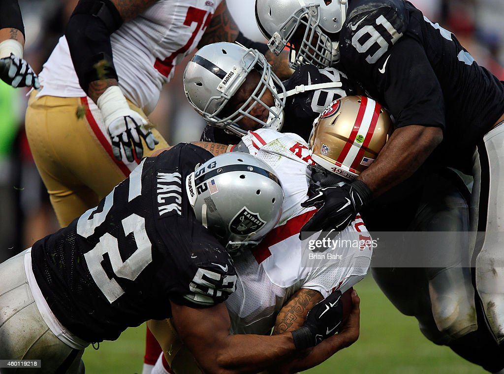 Justin Tuck #91 of the Oakland Raiders, Antonio Smith #94 of the Oakland Raiders, Khalil Mack #52 of the Oakland Raiders sack Colin Kaepernick #7 of the San Francisco 49ers in the fourth quarter at O.co Coliseum on December 7, 2014 in Oakland, California.