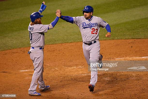 Justin Turner and Adrian Gonzalez of the Los Angeles Dodgers celebrate as they score on a two RBI single by Andre Ethier of the Los Angeles Dodgers...