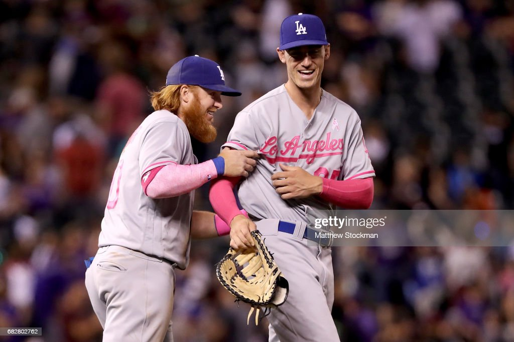 Justin Turner #10 and Cody Bellinger #35 of the Los Angeles Dodgers celebrate their win against the Colorado Rockies at Coors Field on May 13, 2017 in Denver, Colorado. Members of both teams were wearing pink in commemoration of Mother's Day weekend.