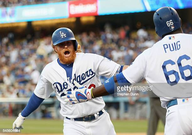 Justin Turner and Yasiel Puig of the Los Angeles Dodgers celebrate as Turner returns to the dugout after hitting a solo home run in the first inning...