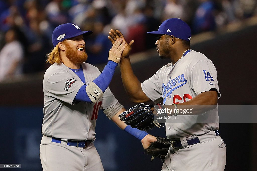 Justin Turner #10 and Yasiel Puig #66 of the Los Angeles Dodgers celebrate after defeating the Chicago Cubs 1-0 in game two of the National League Championship Series at Wrigley Field on October 16, 2016 in Chicago, Illinois.