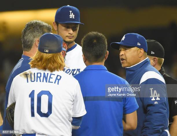 Justin Turner listens as manager Dave Roberts of the Los Angeles Dodgers talks to team trainers as they decide to pull pitcher Yu Darvish at the...