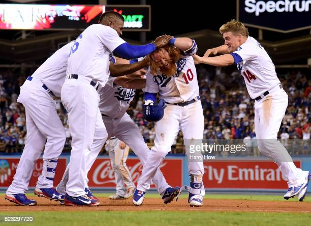 Justin Turner of the Los Angeles Dodger celebrates his game winning single to score a run with Yasiel Puig and Enrique Hernandez for a 65 win over...