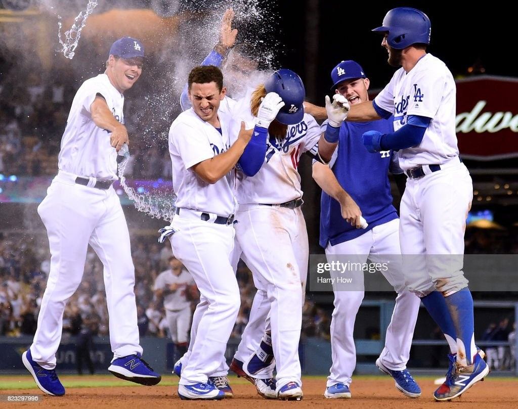 Justin Turner #10 of the Los Angeles Dodger celebrates his game winning single to score a run with Rich Hill #44, Austin Barnes #15, Alex Wood #57 and Chris Taylor #3 for a 6-5 win over the Minnesota Twins, during the ninth inning at Dodger Stadium on July 26, 2017 in Los Angeles, California.