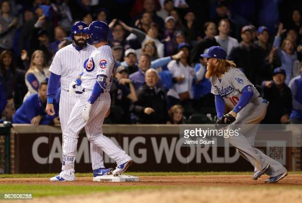 Justin Turner of the Los Angeles Dodgers attempts to tag Alex Avila and Albert Almora Jr #5 of the Chicago Cubs in the ninth inning during game three...